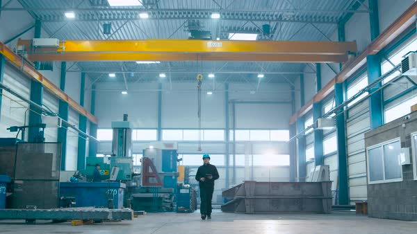 Factory worker in a hard hat is walking through industrial facilities. Royalty-free stock video