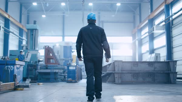 Follow footage of factory worker in a hard hat that is walking through industrial facilities. Royalty-free stock video