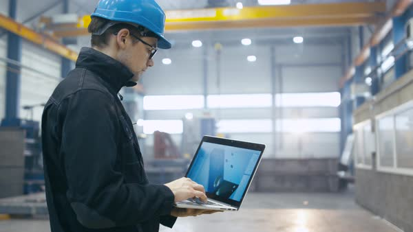 Factory worker in a hard hat is using a laptop computer with an engineering software. Royalty-free stock video
