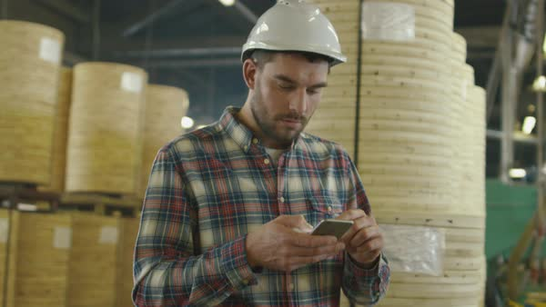 Worker is using a tablet computer in lumber factory warehouse. Royalty-free stock video