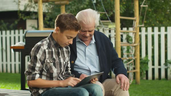 Young Boy Showing to Senior Man how to use Touchscreen Tablet Computer. Royalty-free stock video