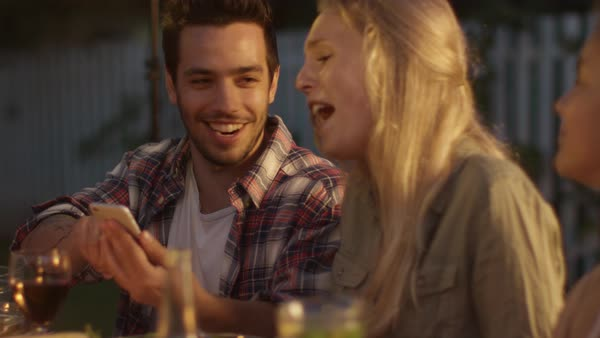 Handsome Man Using Mobile Phone and Showing Content to His Girlfriend during Family Dinner. Royalty-free stock video