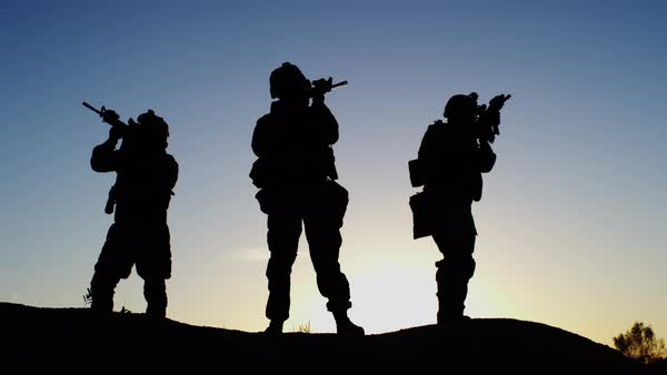 Squad of Three Fully Equipped and Armed Soldiers Standing in Desert Environment in Sunset Light. Slow Motion. Royalty-free stock video