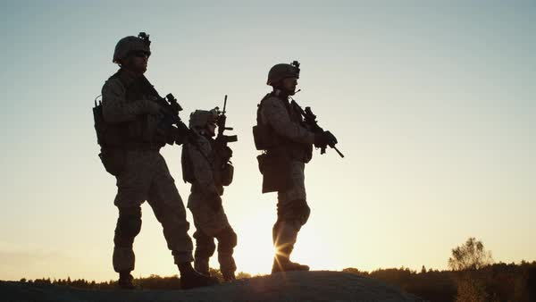 Squad of Three Fully Equipped and Armed Soldiers Standing on Hill in Desert Environment in Sunset Light. Slow Motion. Royalty-free stock video