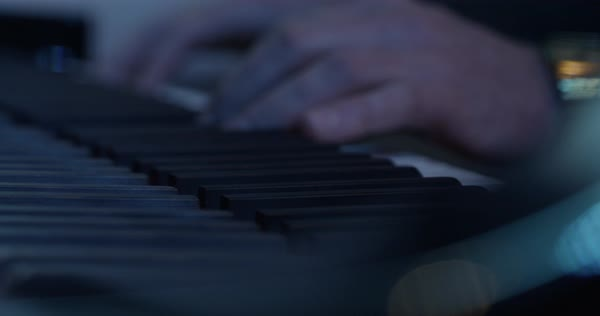 Panning shot of a man playing a piano Royalty-free stock video