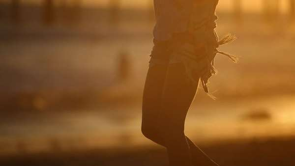 Medium shot of a woman dancing on a beach at sunset Royalty-free stock video