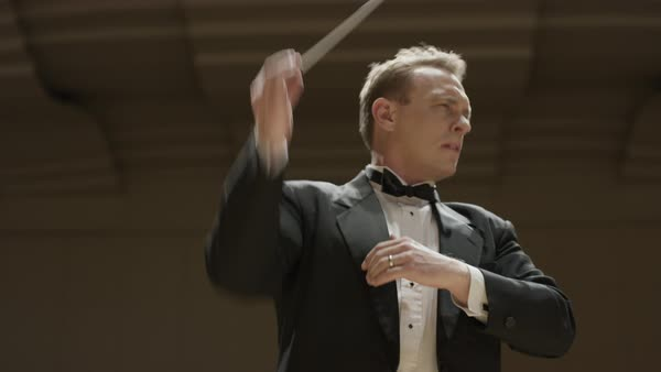 Close up low angle panning shot of orchestra conductor Rights-managed stock video