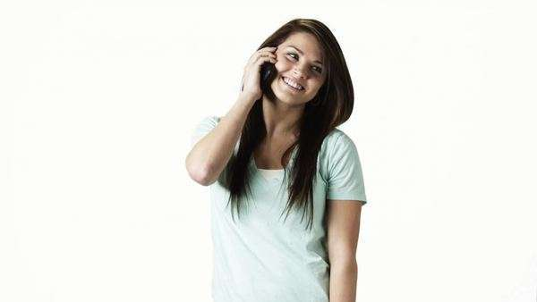 Medium shot portrait of young woman talking on phone against white background Royalty-free stock video