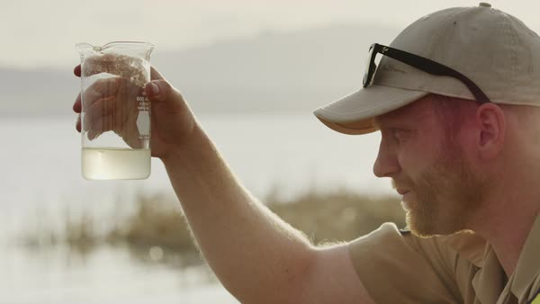 Close up of park ranger collecting water sample from lake Royalty-free stock video