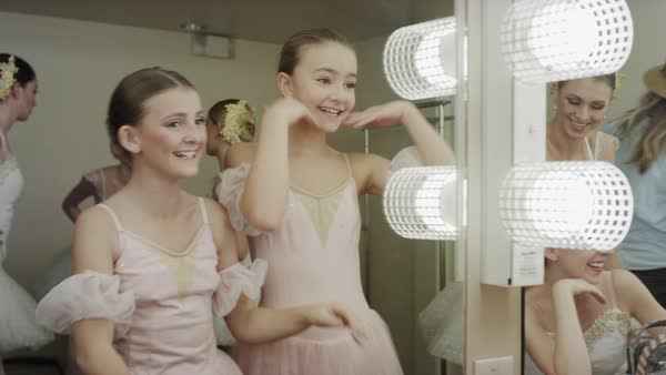 Medium shot of happy ballerinas stretching in dressing room mirror Rights-managed stock video