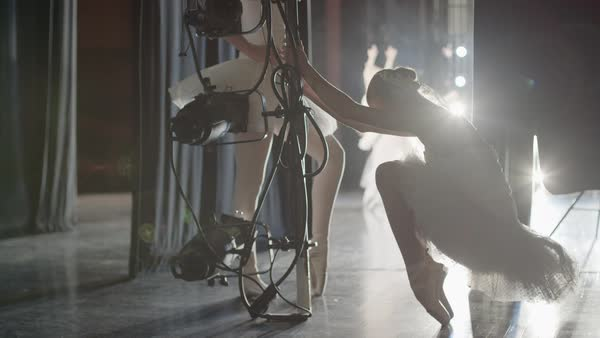 Medium slow motion panning shot of ballerina stretching en pointe backstage Rights-managed stock video