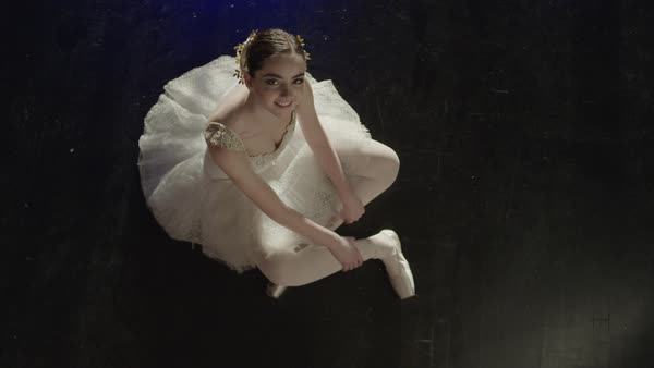 Medium slow motion high angle shot of smiling ballerina sitting on floor Rights-managed stock video