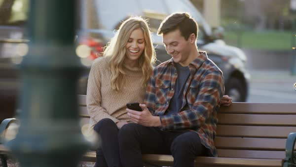 Medium shot of couple sitting on urban bench texting on cell phone Royalty-free stock video