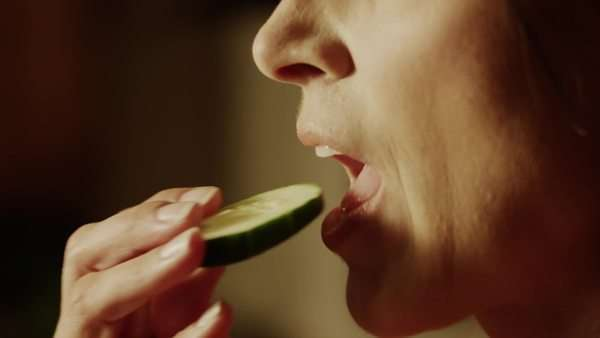 Panning close-up of woman biting into cucumber slice, Cedar Hills, Utah Royalty-free stock video