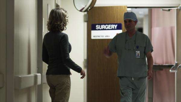 Slow motion medium shot Happy woman embracing surgeon in hospital corridor / Payson, Utah, USA Rights-managed stock video