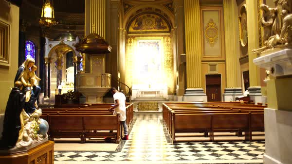 Wide shot of a man taking a seat on a bench in a church in Philadelphia, PA, USA Royalty-free stock video