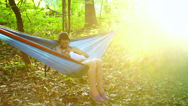 Medium wide shot of a mother sitting in a hammock with her baby Royalty-free stock video