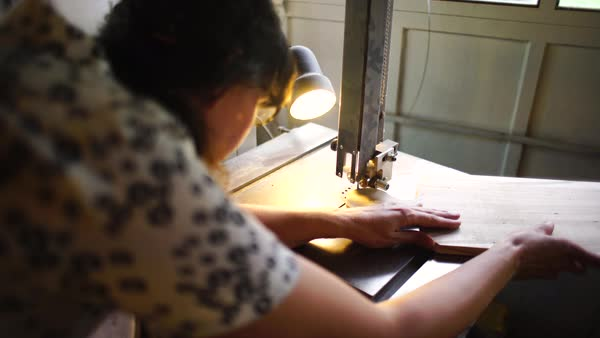 Medium shot of a woman cutting out a piece from a wooden cutting board Royalty-free stock video