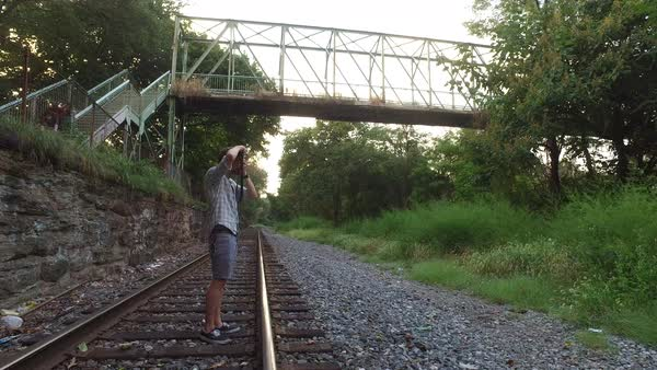 Wide shot of a man taking photographs on a railroad track Royalty-free stock video