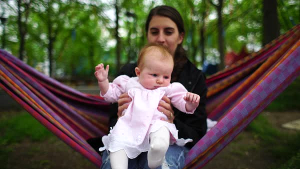 Medium shot of a woman swinging in a hammock with a baby Rights-managed stock video