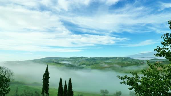 Timelapse. Morning mist go down on the amazing green meadow of Tuscany, Italy, fast movement of clouds over the endless blue sky. Beautiful landscape with meadows and fields, green grass and trees Royalty-free stock video