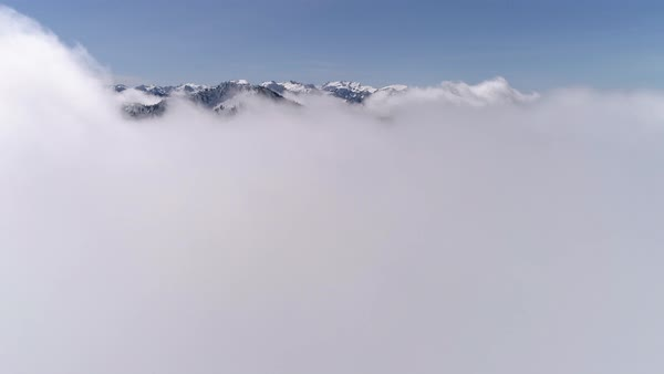 Aerial Above Clouds with Snowy Tops of Cascade Mountain Range and Blue Sky Royalty-free stock video