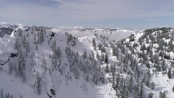 Beautiful Day in Winter Wonderland with Aerial of Snowy Mountain Forest and Lowland Fog Clouds Royalty-free stock video