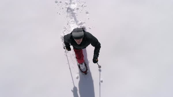Overhead Aerial Close Up of Man Running Slow Motion with Snowshoes in Fresh Deep Powder Snow Royalty-free stock video