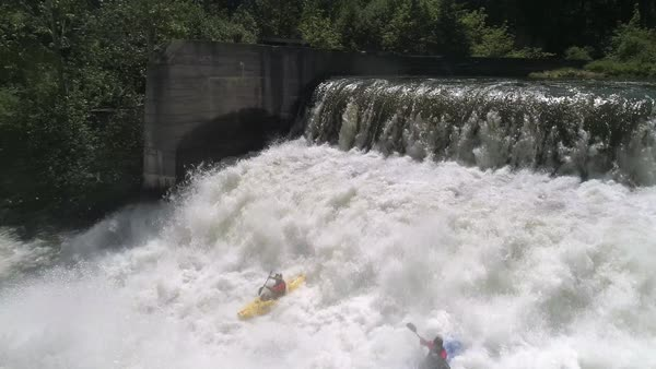 Aerial of 2 extreme kayakers kayaking over dam waterfall white water cliff edge Royalty-free stock video