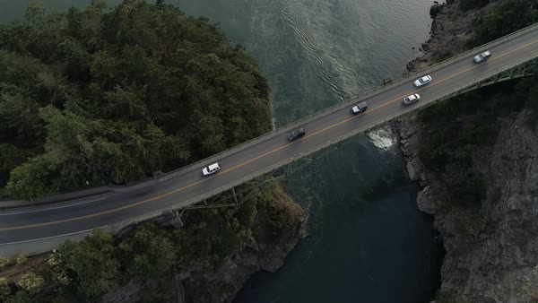 Overhead aerial above cars traveling on high canyon bridge crossing blue ocean water Royalty-free stock video
