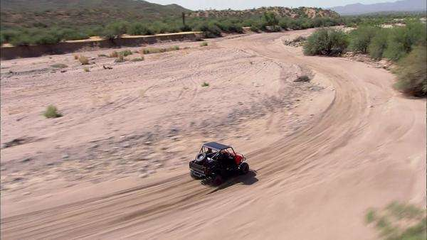 Aerial footage of the Arizona desert  A man is riding a dune buggy through  the desert  stock footage