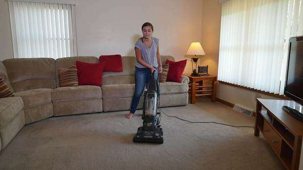 A teenager uses the vacuum cleaner while listening to her iPod in her home. Royalty-free stock video