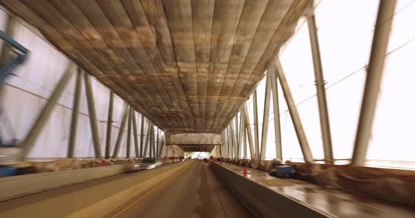 A personal perspective of driving onto a bridge in western Pennsylvania that is tented for painting and repairs. Royalty-free stock video