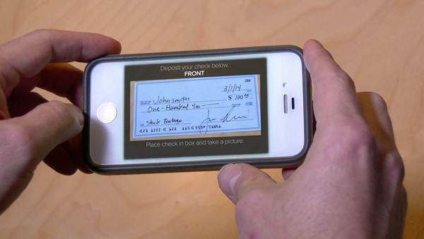 Depositing a check with a mobile phone. Check and phone interface are both fictional. Royalty-free stock video