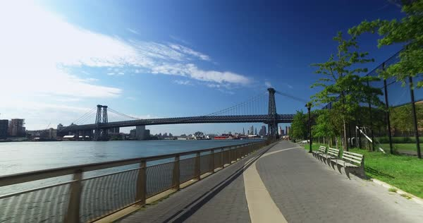 A bike rider's forward perspective on the East River Bikeway with the Williamsburg Bridge in the background.  	 Royalty-free stock video