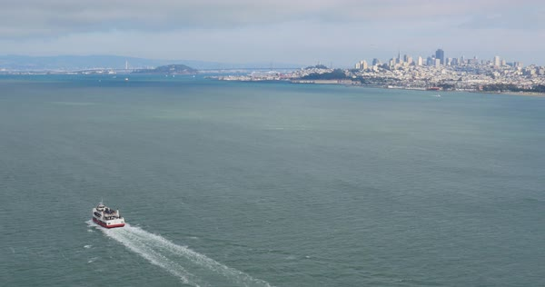 A high angle view of the San Francisco skyline in the distance as a tour boat travels in the Bay. Royalty-free stock video