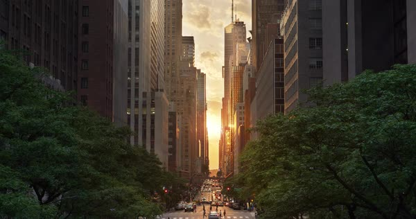 "A cinematic wide evening establishing shot over 42nd Street in New York City during a ""Manhattanhenge"" sunset event.  Royalty-free stock video"