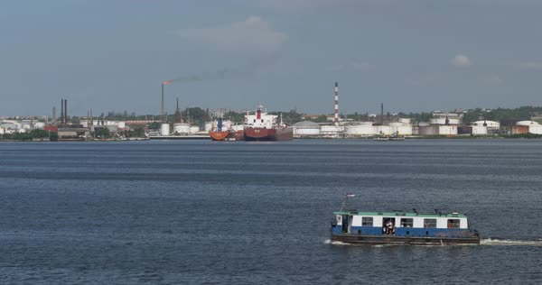 A ferry boat carries passengers past a factory and smoke stacks on Havana Port Bay. Royalty-free stock video
