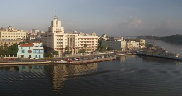 A high angle stationary establishing shot of traffic and pedestrian activity along the shoreline of Havana, Cuba at sunrise.  Royalty-free stock video