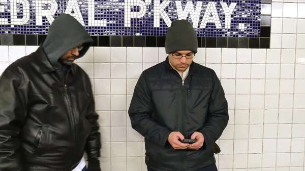A man steals another man's cell phone while he's texting on a Manhattan subway platform. Royalty-free stock video