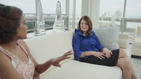 Medium shot of two women talking in a living room Royalty-free stock video
