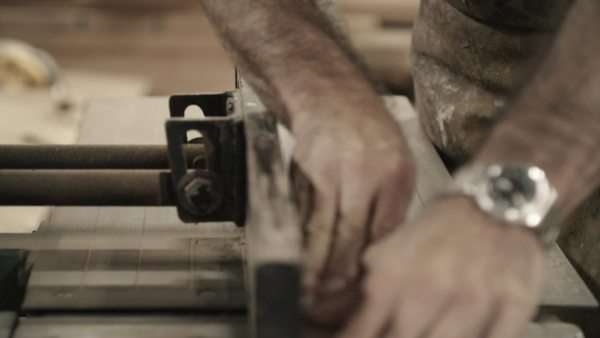 Handheld close-up of a man cutting a piece of wood on a jointer Royalty-free stock video