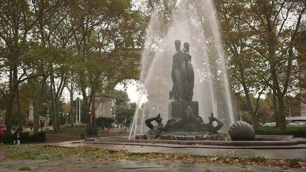 Brooklyn, New York City: Wide-angle shot of female joggers passing by Bailey Fountain on overcast day Royalty-free stock video
