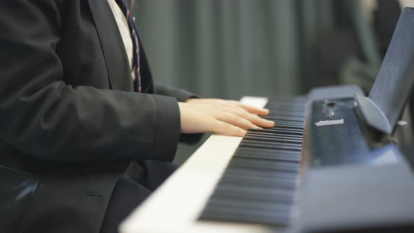 Teen girl singing solo and playing keyboard instrument in school music lesson Royalty-free stock video