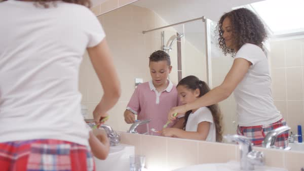 Happy family in bathroom   mother   2 children brushing their teeth  together  Royalty. Cute young brother   sister in bathroom  looking in mirror