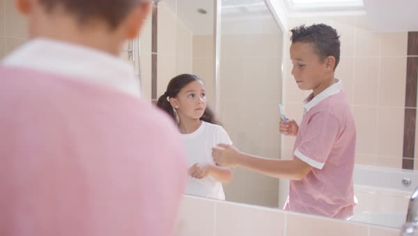 Cute young brother   sister in bathroom  looking in mirror   brushing teeth  Royalty. Cute young brother   sister in bathroom  looking in mirror