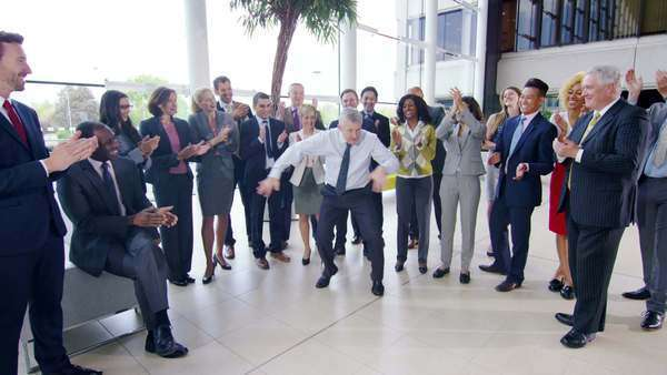 Self confident businessman doing funny dancing to entertain his colleagues Royalty-free stock video