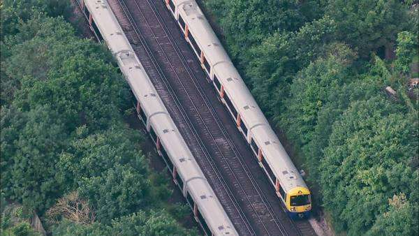 Aerial view of two passenger trains passing by each other in opposite direction over the suburbs of London Royalty-free stock video