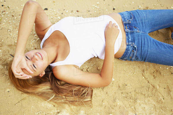 10da2d5fe4735 Portrait of a young woman laying on the sand Kauai hawaii united states of  america - Stock Photo - Dissolve