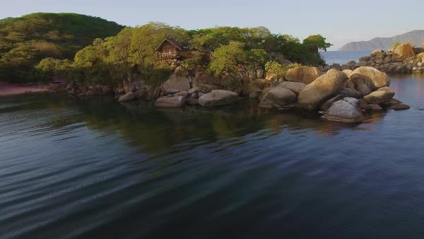 Aerial drone shot of luxury water front hotel resort on island, rustic eco  bungalow accommodation on exotic island in lake Malawi  stock footage